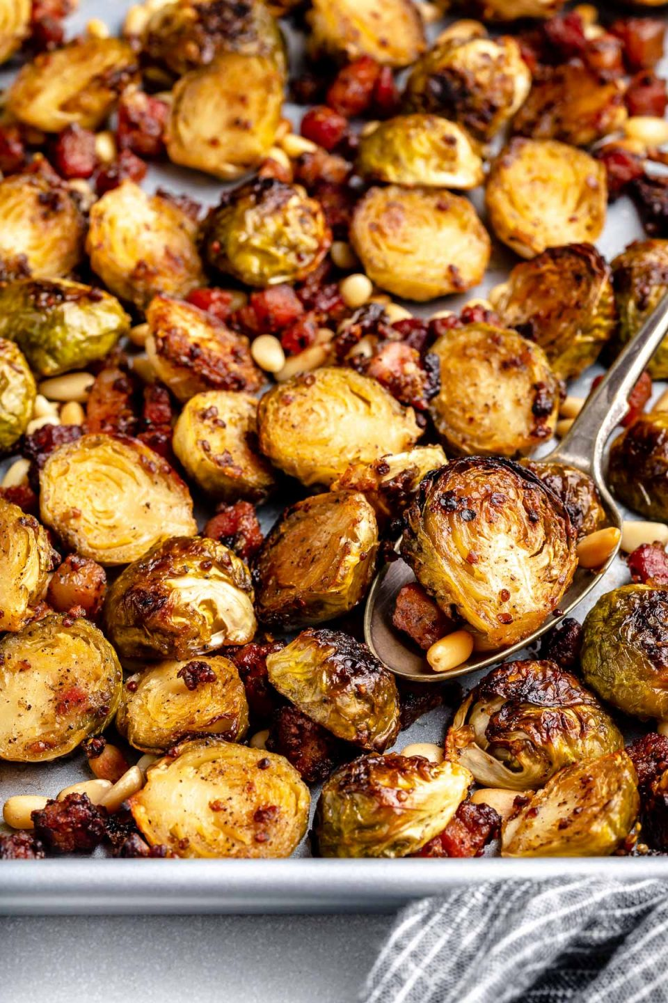 Close view of maple mustard roasted brussels sprouts with pancetta & pine nuts on a large baking sheet. The baking sheet sits atop a light blue surface next to a striped blue linen napkin.