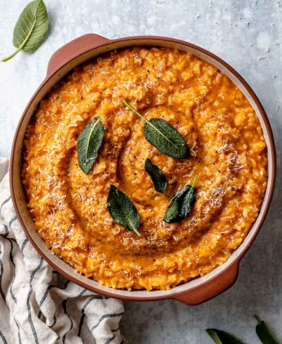 Creamy pumpkin risotto shown in a large terra cotta serving dish. The risotto is topped with crispy fried sage leaves & finely grated parmesan. The dish sits atop a light blue surface, next to a striped linen napkin & some fresh sage leaves.