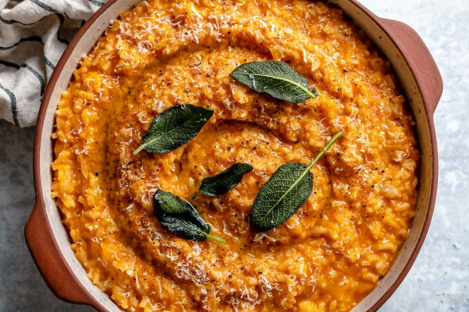 Creamy pumpkin risotto shown in a large terra cotta serving dish. The risotto is topped with crispy fried sage leaves & finely grated parmesan. The dish sits atop a light blue surface, next to a striped linen napkin.