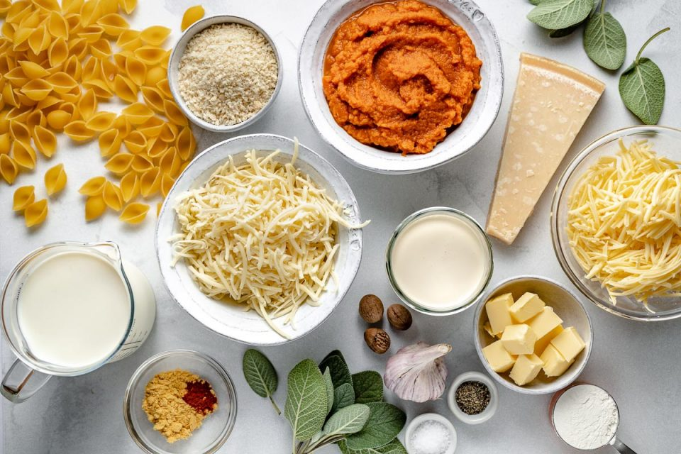 Pumpkin Mac & Cheese ingredients arranged on a light blue surface: pasta shells, milk, spics, cheddar, parmesan, cream, gruyere, butter, flour, garlic, nutmeg & fresh sage leaves.