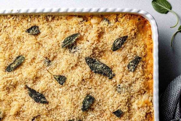 Pumpkin Mac & Cheese topped with Brown Butter Sage Breadcrumbs in a large white baking dish.