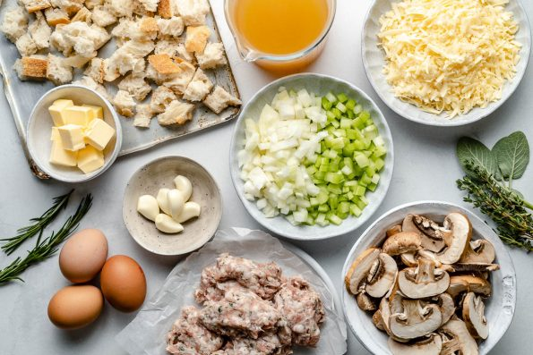 Homemade stuffing ingredients: sourdough bread cubes, butter, herbs, eggs, garlic, sage pork sausage, mushrooms, onions, celery, chicken stock & cheese.