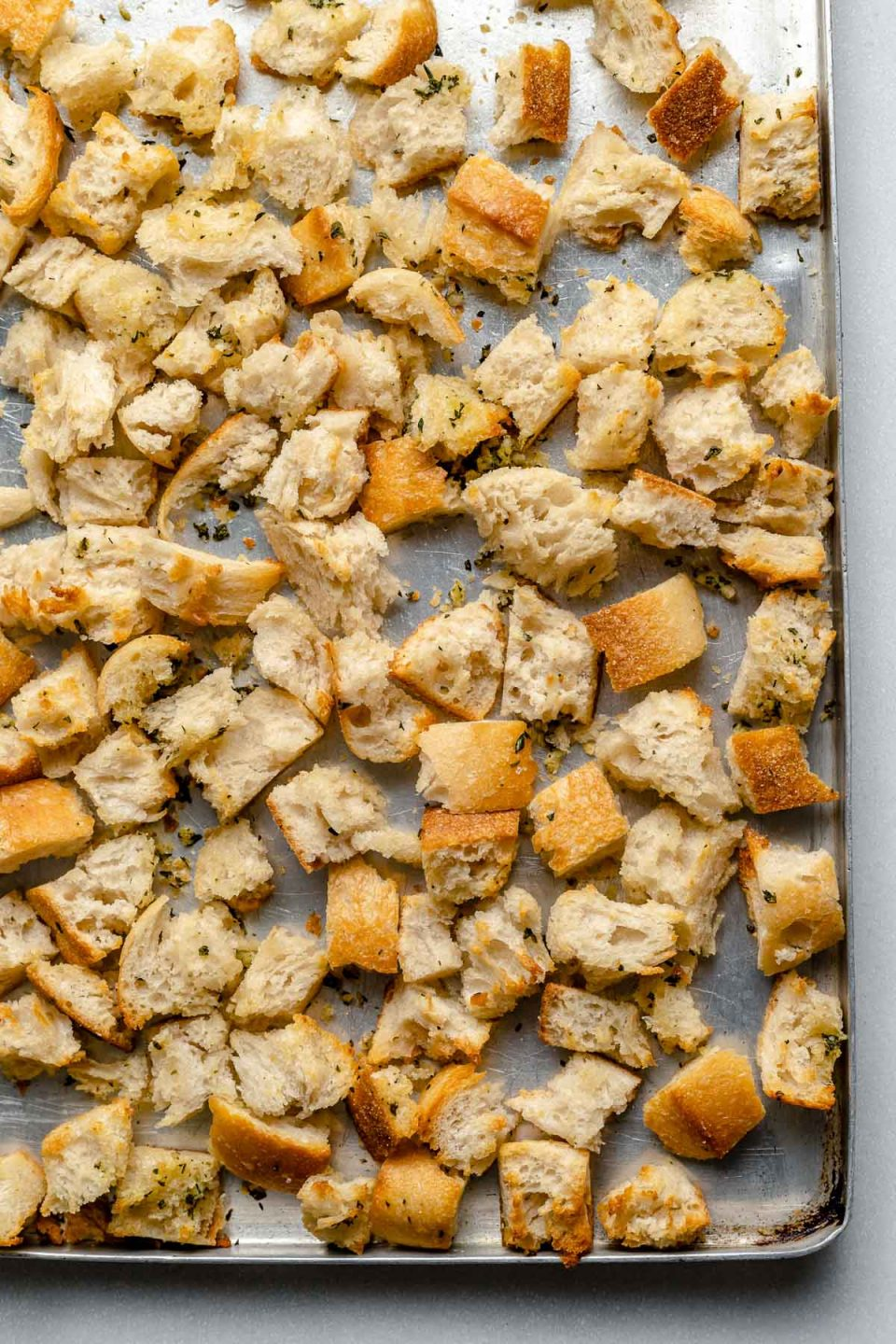 Homemade herbed sourdough bread cubes on a large baking sheet.