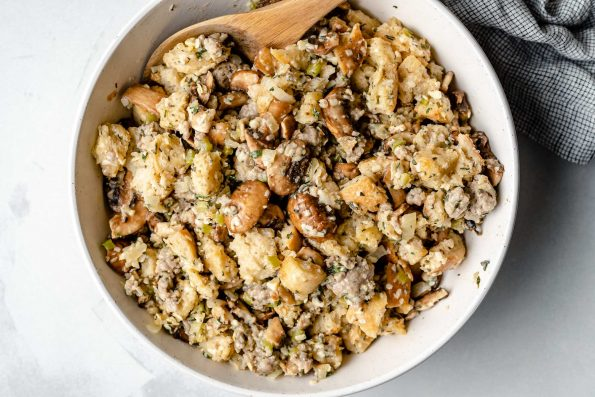 Mixing homemade stuffing together in a large white mixing bowl with a wooden spoon. The bowl sits atop a light blue surface next to a checkered linen napkin.