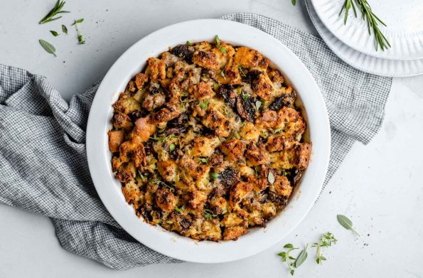 Baked sourdough sausage stuffing in a round baking dish. The dis sits atop a checkered linen napkin on a light blue surface next to a stack of plates & some fresh herbs.
