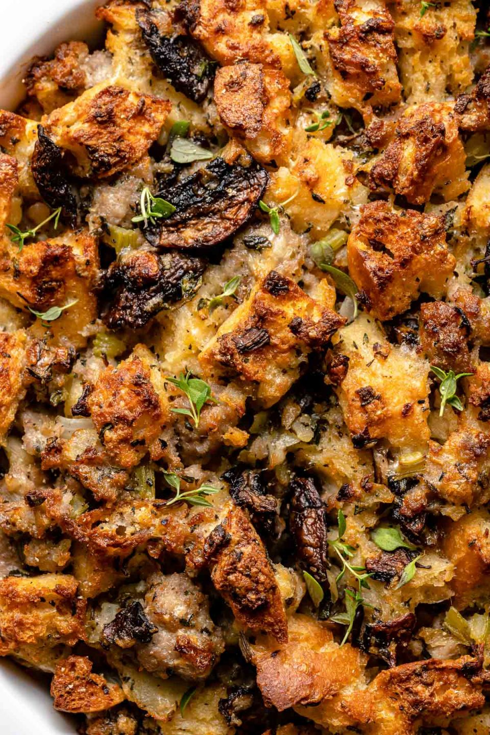 Close view of top of baked sourdough stuffing. The stuffing is topped with fresh thyme.