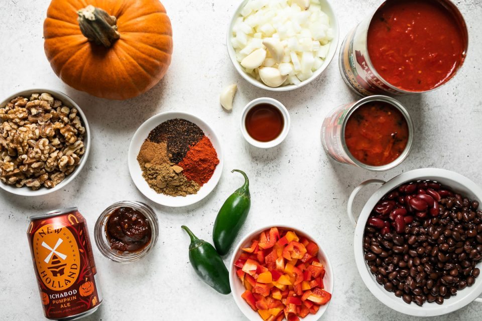 Pumpkin chili ingredients arranged on a white surface: a bowl of walnuts, small sugar pumpkin, Ichabod Pumpkin Ale, jar of chipotle peppers, plate of chili spices, bowl of diced onions & garlic cloves, 2 jalapeno peppers, bowl of diced peppers, black beans & kidney beans in small white colander, 2 cans of crushed tomatoes.