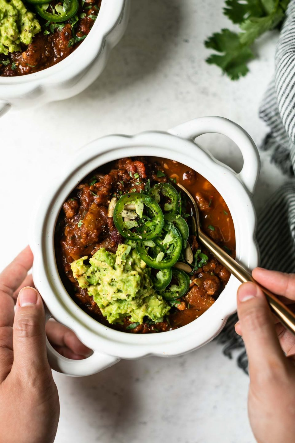 Vegan pumpkin chili shown in a white, pumpkin-shaped bowl. A woman's hands hold the bowl & a gold spoon, taking a spoonful of chili out of the bowl. The bowl sits atop a white surface, nestled next to a striped linen napkin. A second bowl of chili peeks into the top of the frame.