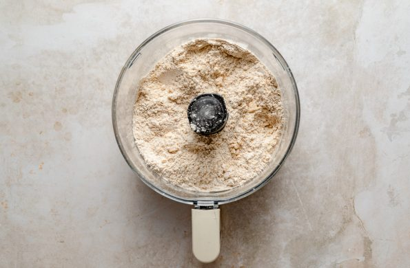 Scone dry mix shown in a food processor bowl atop a creamy marble surface.