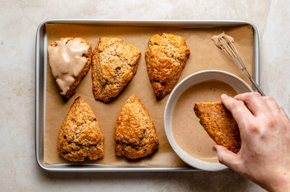 Dipping chai scones in maple glaze. Baked scones & bowl of glaze atop a parchment-lined baking sheet. A woman's hand dunks 1 of the scones into the glaze.
