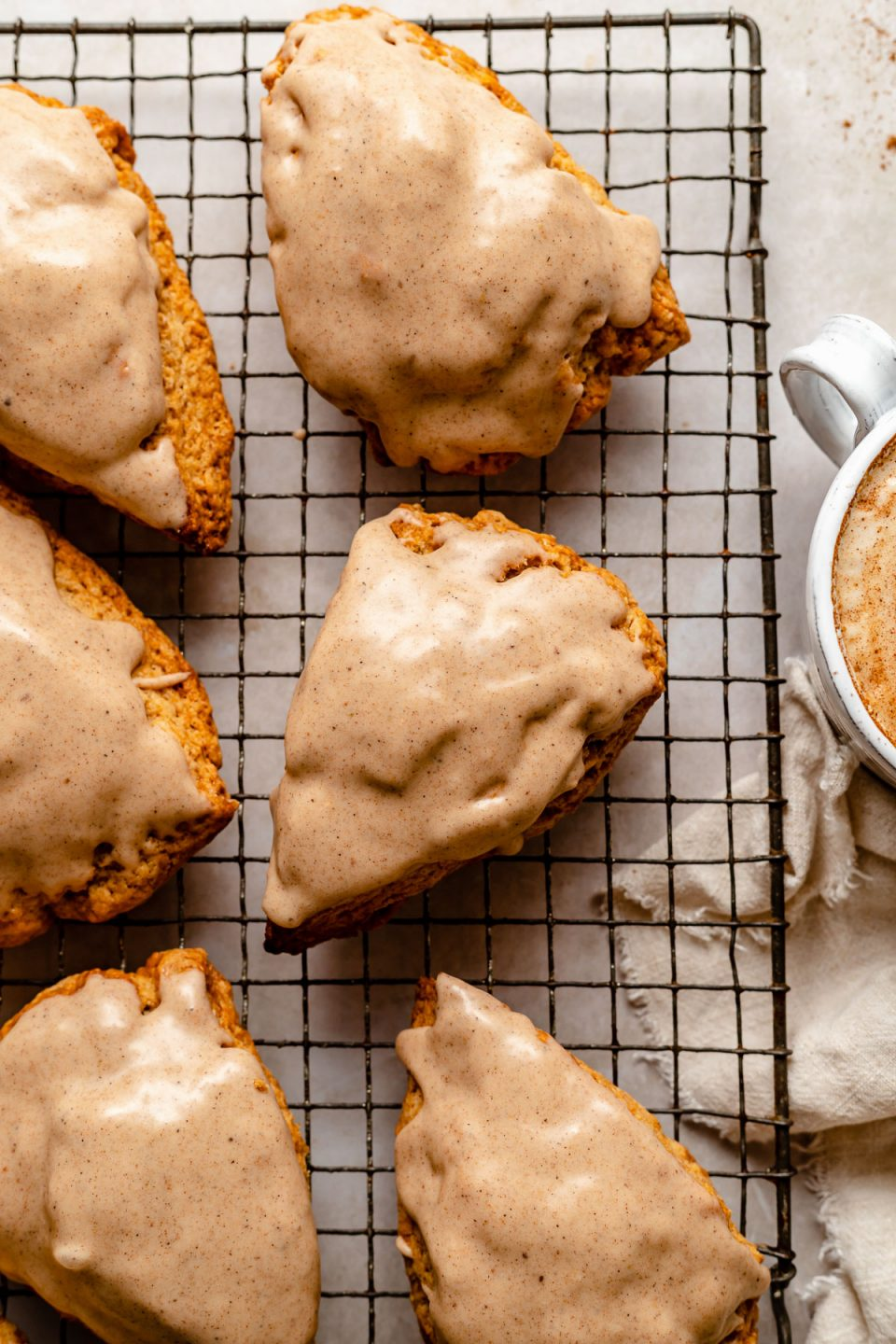 Glazed Chai Scones sit atop a metal baking rack. Next to the rack are a beige linen napkin, a whole cinnamon stick, & a mug with a chai latte in it.