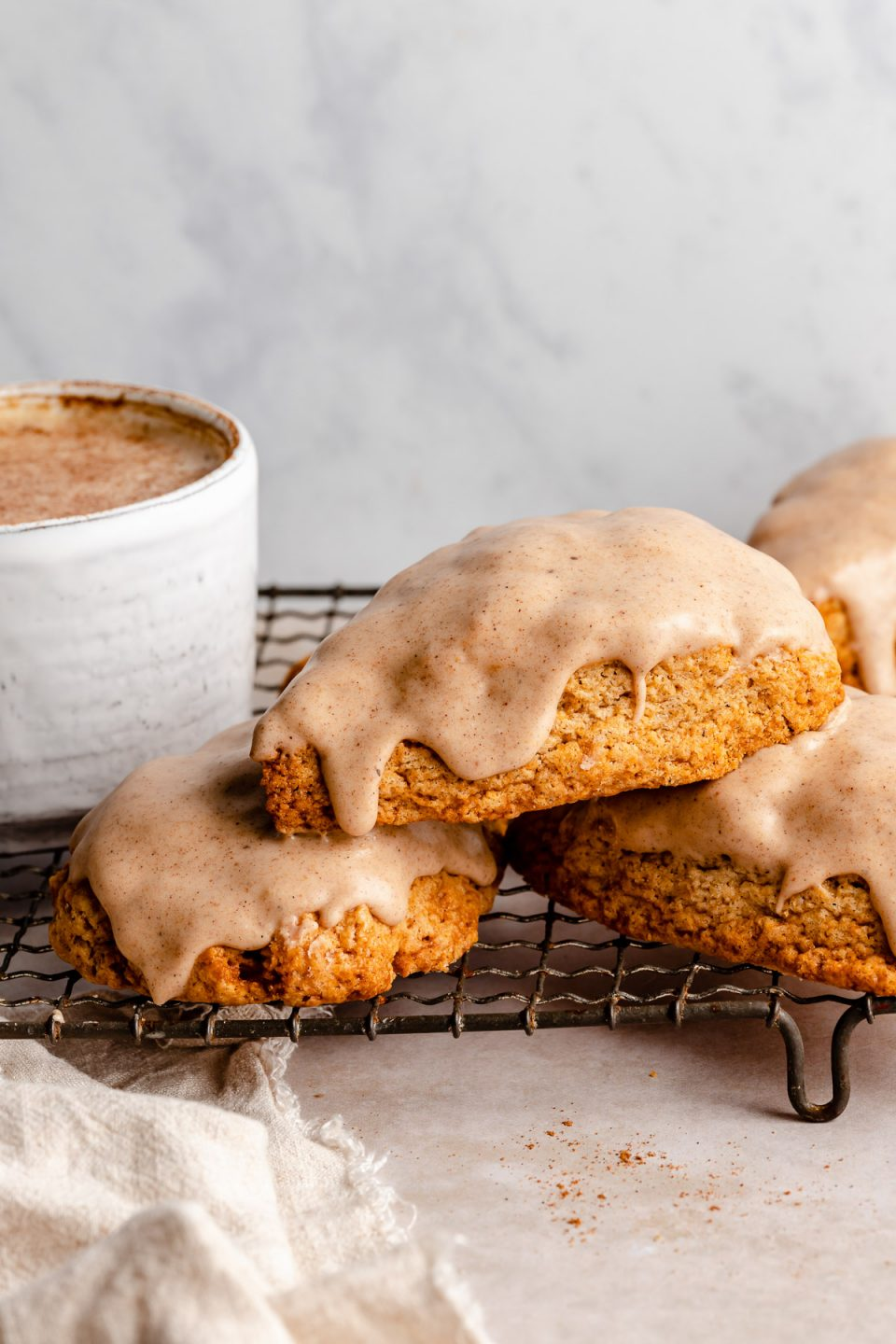Glazed chai scones stacked atop a wire baking rack, next to a chai latte in a ceramic mug.