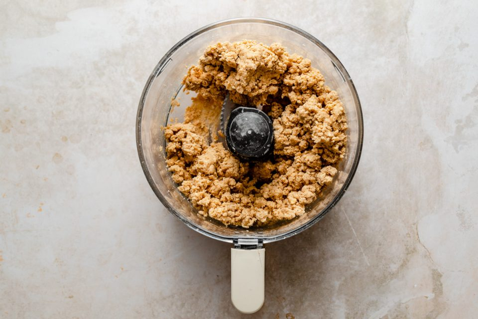 Scone dough shown in a food processor bowl atop a creamy marble surface.