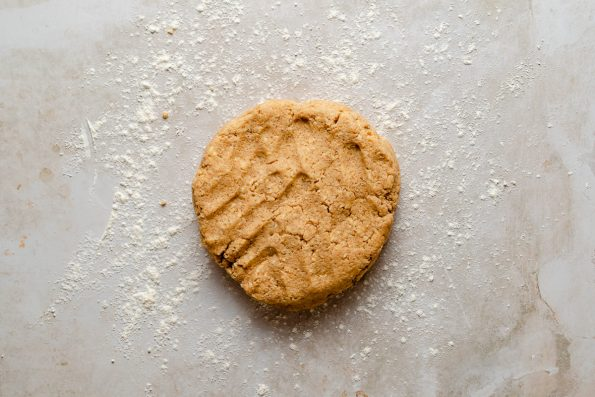 Scone dough rolled into a disc atop a lightly floured creamy marble surface.