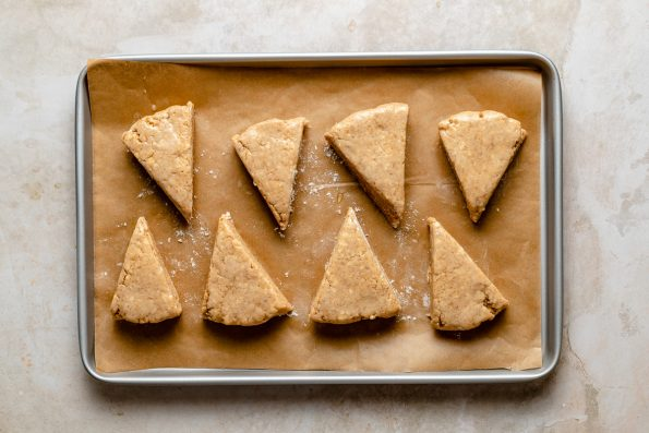 unbaked scones arranged on a parchment-lined baking sheet atop a creamy marble surface.