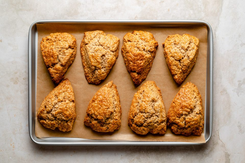 Baked chai spice scones arranged on a parchment-lined baking sheet atop a creamy marble surface.
