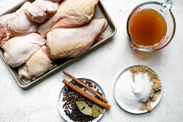 Apple Cider Chicken ingredients arranged on a white surface: a small sheet pan with bone-in skin-on chicken parts, apple cider, salt, brown sugar, whole cinnamon sticks, bay leaves, cloves, & allspice berries.