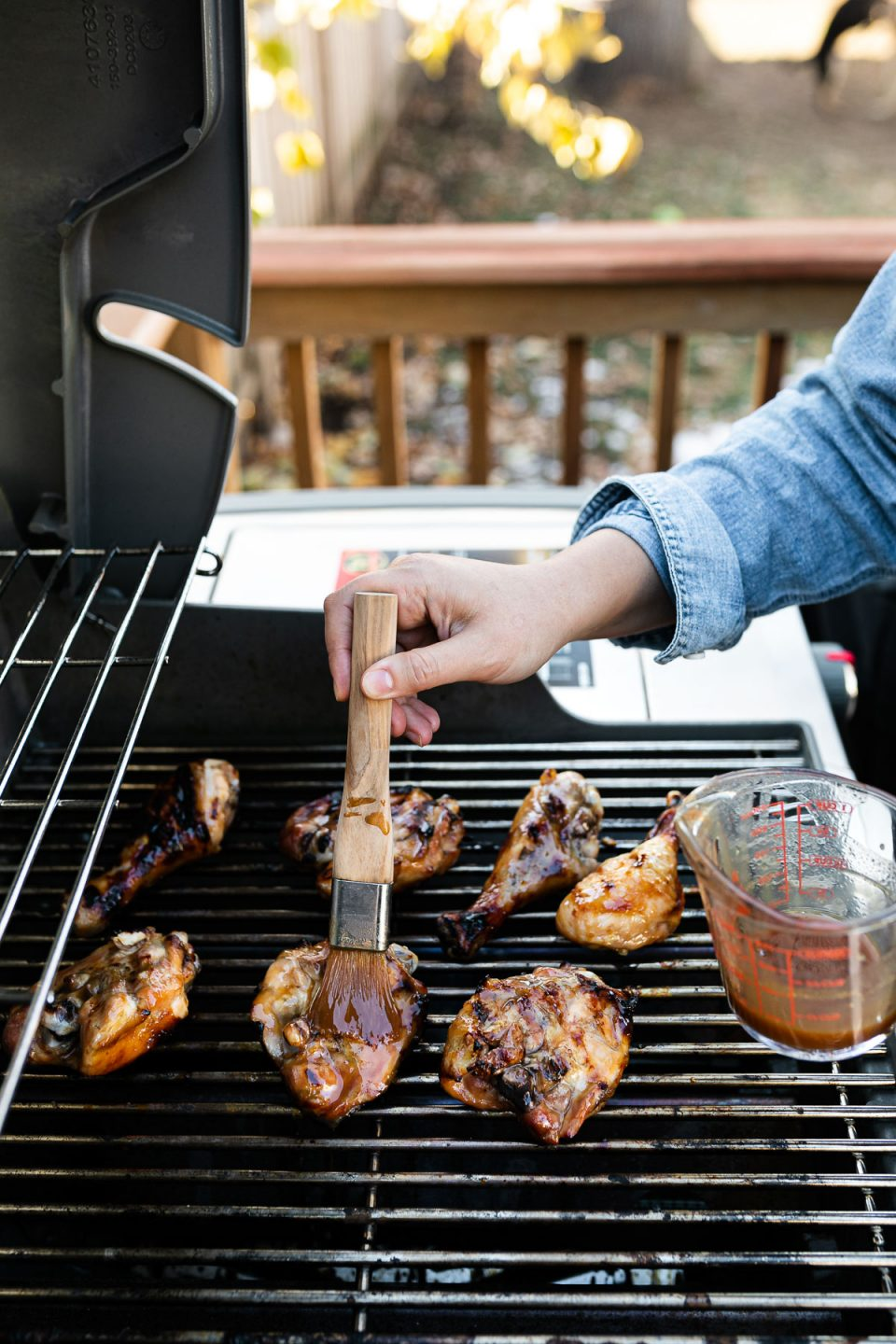 Woman's hands brushing apple cider glaze on grilled chicken.