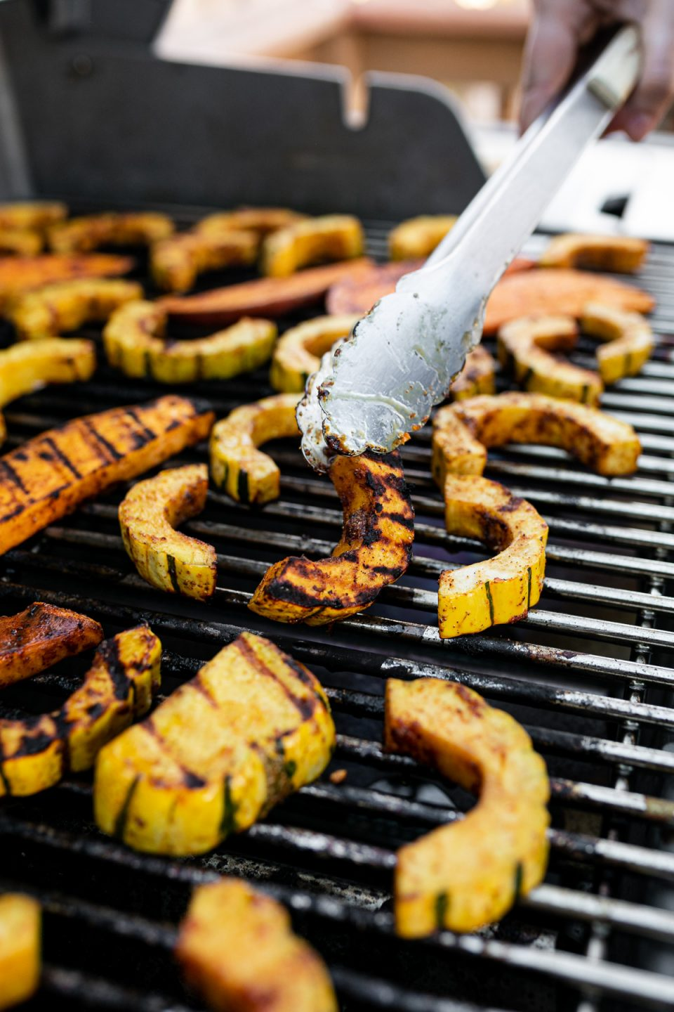 Grill tongs reaching into frame, flipping spiced delicata squash on the grill grates.