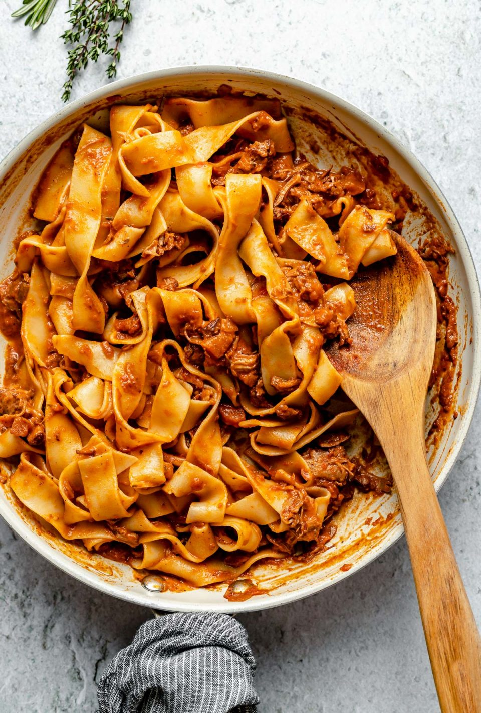 Lamb ragu pappardelle in a small skillet atop a light blue surface. A wooden spoon is nestled into the pasta. Next to the skillet are some fresh herbs.