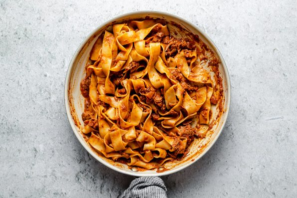 Lamb ragu pappardelle in a small skillet atop a light blue surface.