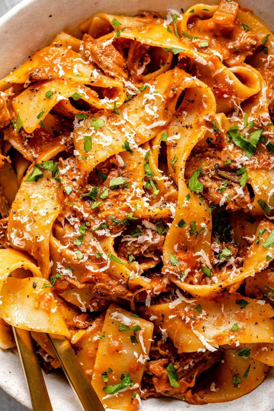 Close up of lamb ragu pappardelle, topped with freshly grated parmesan & chopped parsley.