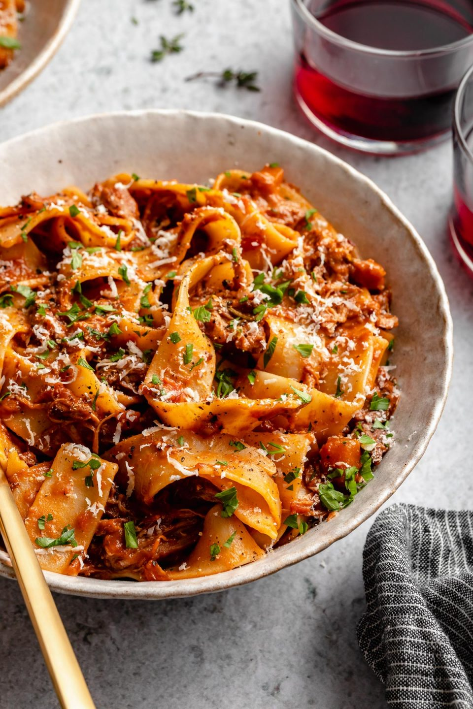 Side angle of Braised Lamb Ragu Pappardelle shown in pasta bowls, topped with grated parmesan & fresh parsley. The bowls sit atop a light blue surface next to fresh herbs, 2 glasses of red wine & a grey striped linen napkin.