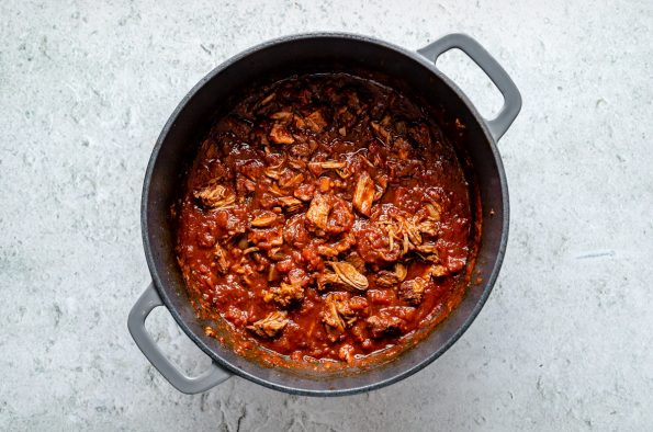 Braised lamb ragu in a large Dutch oven atop a light blue surface.
