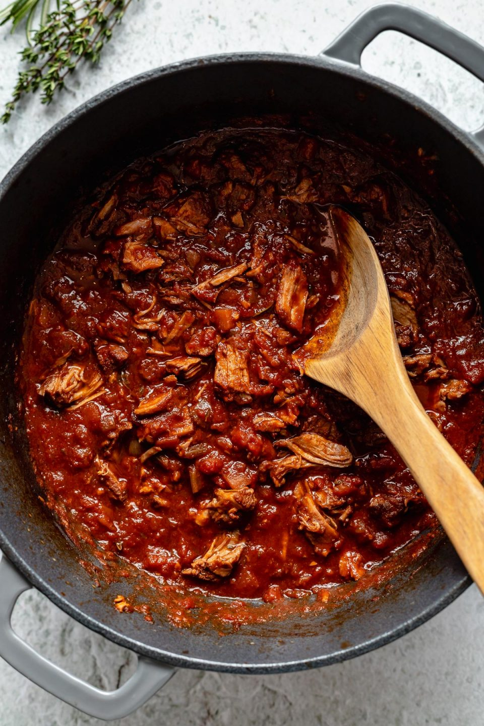 Braised lamb ragu in a large Dutch oven atop a light blue surface. There is a wooden spoon nestled in the ragu sauce & there are fresh herbs next to the pot.
