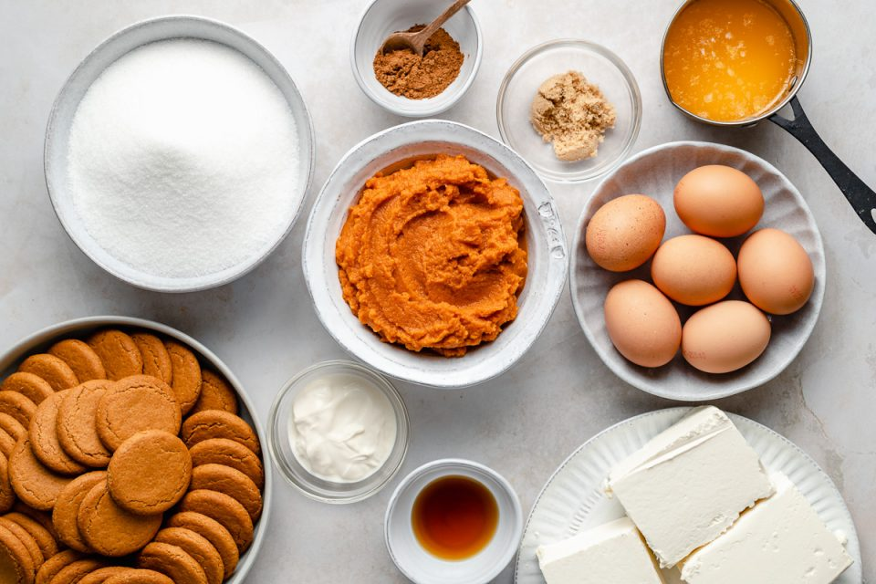 Pumpkin cheesecake ingredients: gingersnap cookies, sugar, pumpkin spices, vanilla extract, pumpkin puree, eggs, cream cheese & sour cream.