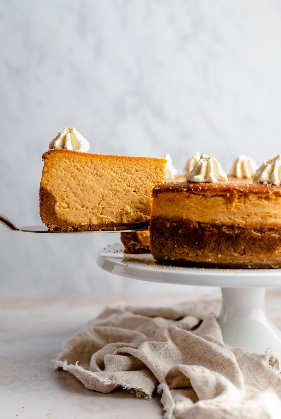 Pulling a slice of pumpkin cheesecake out of the cheesecake with a cake server.