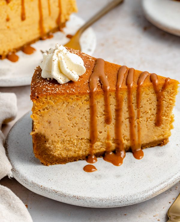 Side angle of pumpkin cheesecake with gingersnap crust. The cheesecake is on a small white ceramic plate, topped with drizzly caramel & freshly whipped cream.