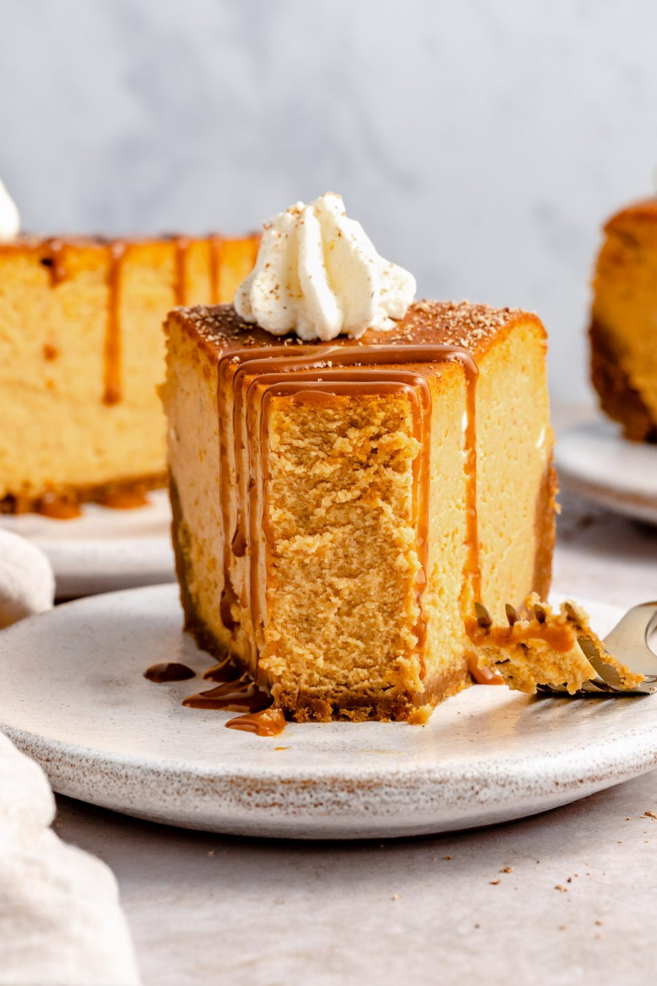 A bite taken out of a slice of pumpkin cheesecake.