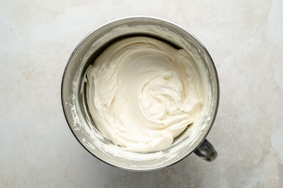 Whipped cream cheese in large stainless steel mixing bowl.