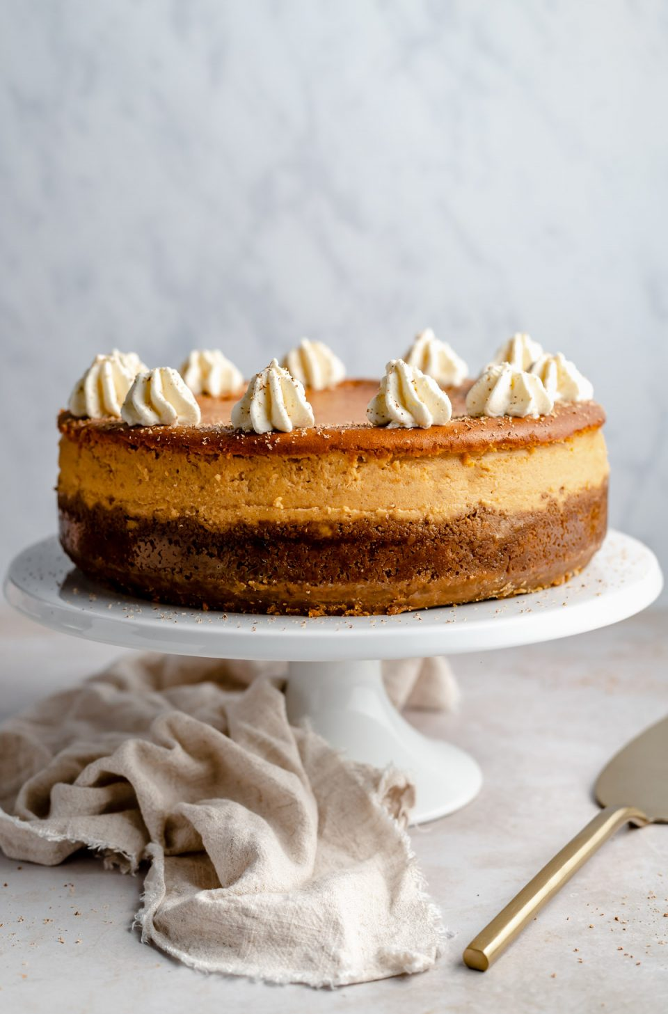 Pumpkin cheesecake with gingersnap crust, displayed on a white cake stand next to a beige linen napkin & a gold cake server.