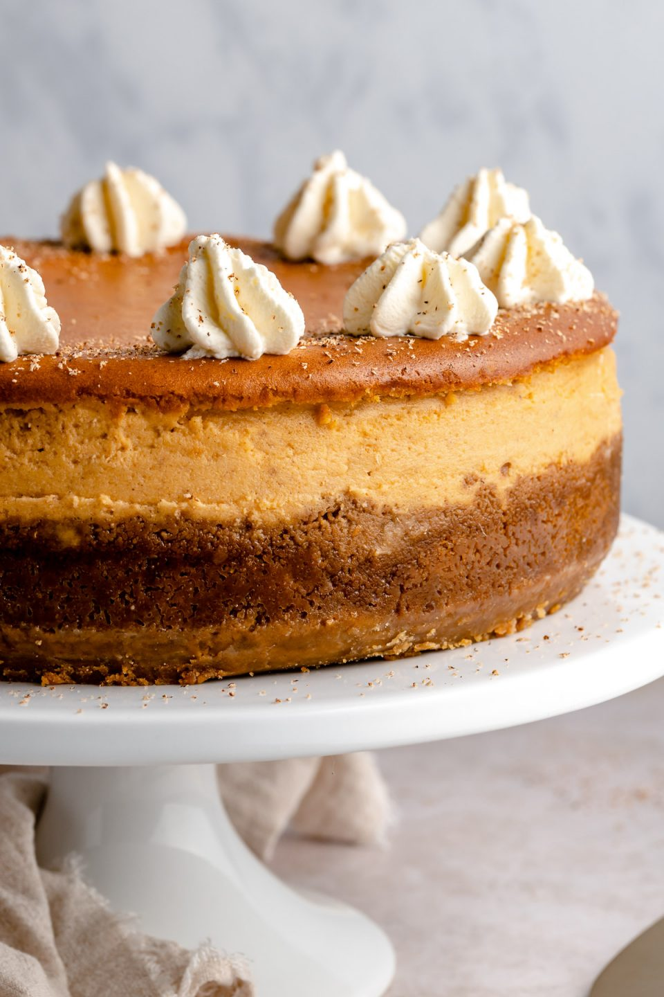 Close up of baked pumpkin cheesecake. The cheesecake is on a white cake stand, topped with piped whipped cream & freshly grated nutmeg.