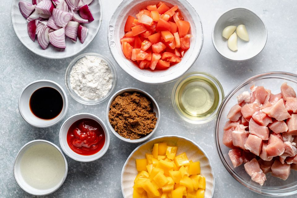 Sweet and sour pork ingredients arranged on a light blue surface in individual bowls & dishes: red onion, rice flour, soy sauce, ketchup, brown sugar, rice vinegar, oil, garlic, tomatoes, bell peppers, & diced pork loin.