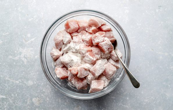 Diced pork loin tossed in rice flour in a large glass mixing bowl atop a light blue surface.