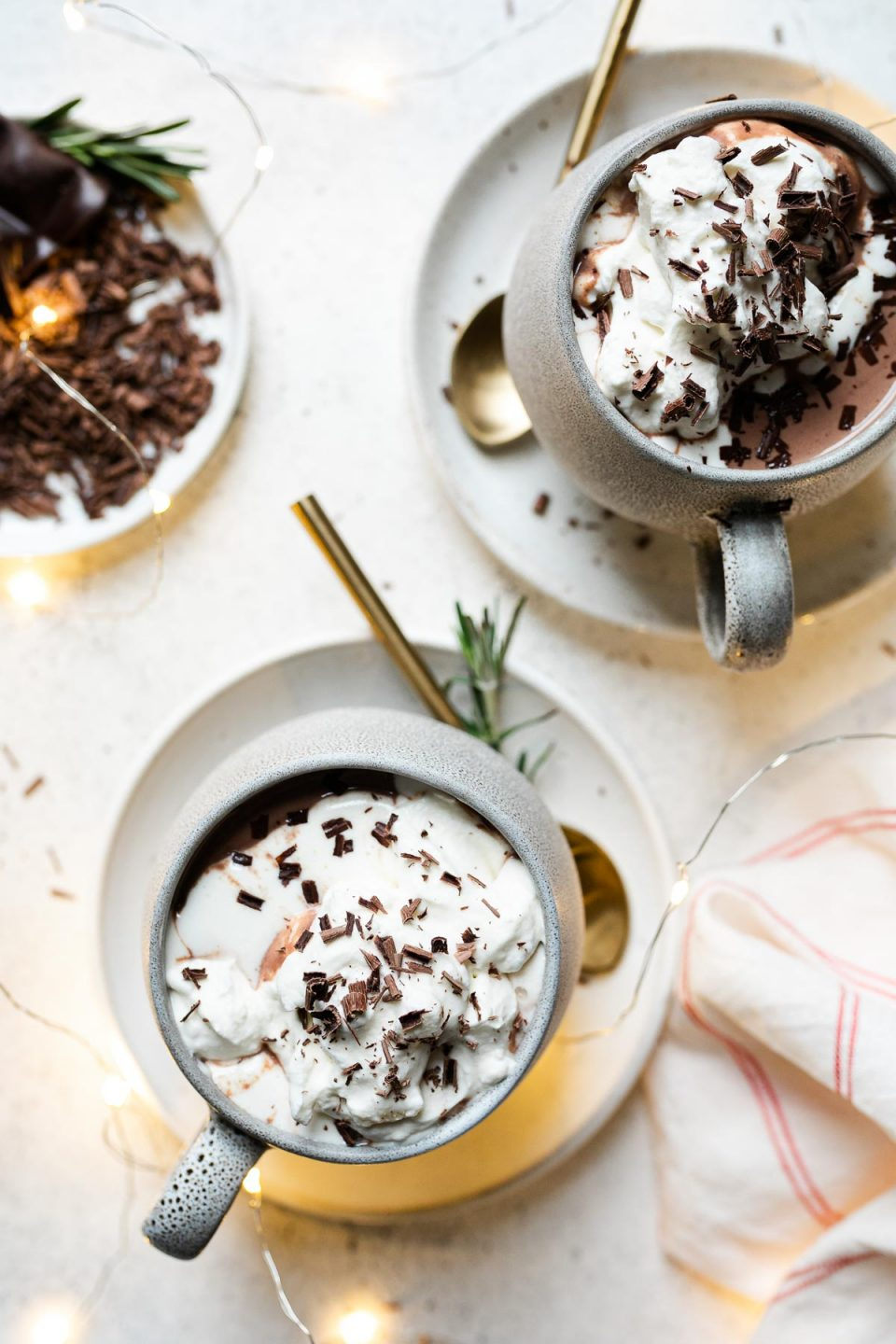 Christmas hot chocolate shown in 2 gray mugs, which sit atop 2 white saucers. The cocoa is topped with freshly whipped cream & shaved chocolate. The saucers sit atop a white surface, next to a red & white striped linen napkin & a small white plate of shaved chocolate.