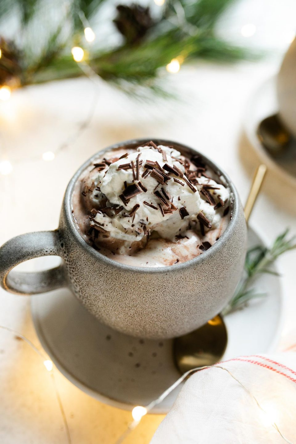 Christmas hot chocolate shown in a gray mug, which sit atop a white saucers. The cocoa is topped with freshly whipped cream & shaved chocolate. The saucer sit atop a white surface, next to a red & white striped linen napkin, twinkly lights, & decorative pine tree.