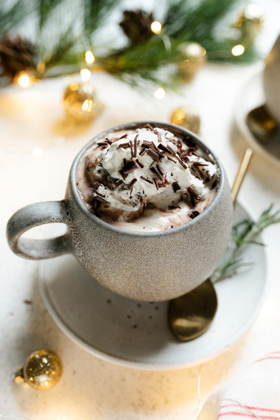 Christmas hot chocolate shown in a gray mug, which sit atop a white saucers. The cocoa is topped with freshly whipped cream & shaved chocolate. The saucer sit atop a white surface, next to a red & white striped linen napkin, twinkly lights, Christmas ornaments, & decorative pine tree.