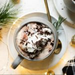 Christmas hot chocolate shown in 2 gray mugs, which sit atop 2 white saucers. The cocoa is topped with freshly whipped cream & shaved chocolate. The saucers sit atop a white surface, next to a black plaid linen napkin, twinkly lights, Christmas ornaments, & decorative pine tree.