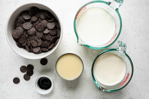 Homemade hot chocolate ingredients arranged on a white surface: bittersweet chocolate wafers, vanilla extract, sweetened condensed milk, heavy cream & whole milk.