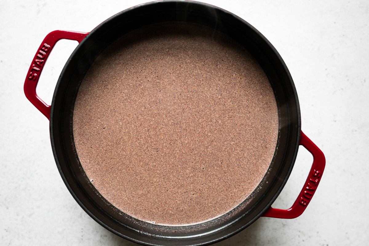 How to make homemade hot cocoa: chocolate melted (even more) into the milk mixture in a red Staub dutch oven, which sits atop a white surface.