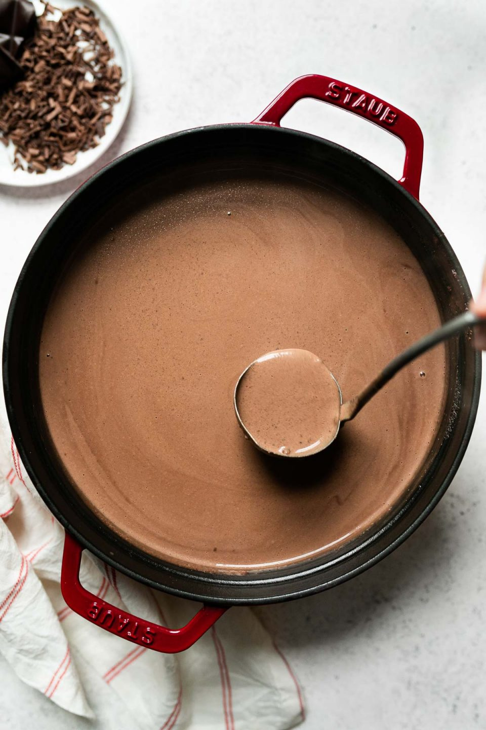 Smooth & creamy hot cocoa in a red Staub dutch oven, which sits atop a white surface. A ladle is shown stirring the cocoa. Next to the dutch oven are a white & red striped linen napkin & a small plate of shaved chocolate.