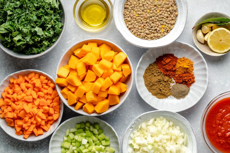 Lentil soup ingredients arranged on a light blue surface: shredded kale, chopped carrots, butternut squash, celery, onion, crushed tomatoes, spices, garlic, lemon, olive oil & brown lentils.