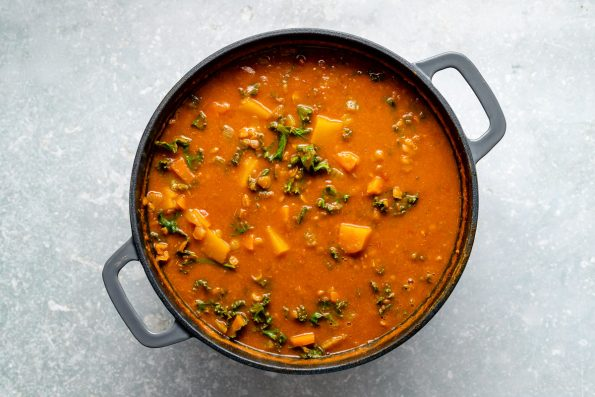 Vegan lentil soup shown in a large gray dutch oven atop a light blue surface.