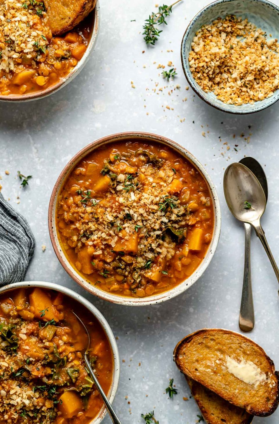 Vegan lentil soup, topped with toasted breadcrumbs, served in 3 speckled ceramic bowls. The bowls sit atop a light blue surface. The bowls are surrounded by crusty buttered bread, spoons, and a sprinkling of fresh herbs & breadcrumbs.