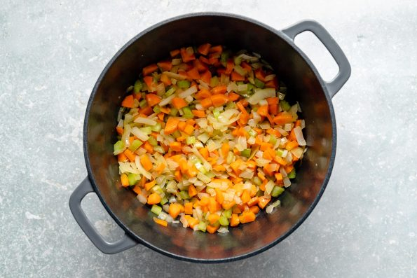 How to make lentil soup: Mirepoix softening in a large gray dutch oven atop a light blue surface.