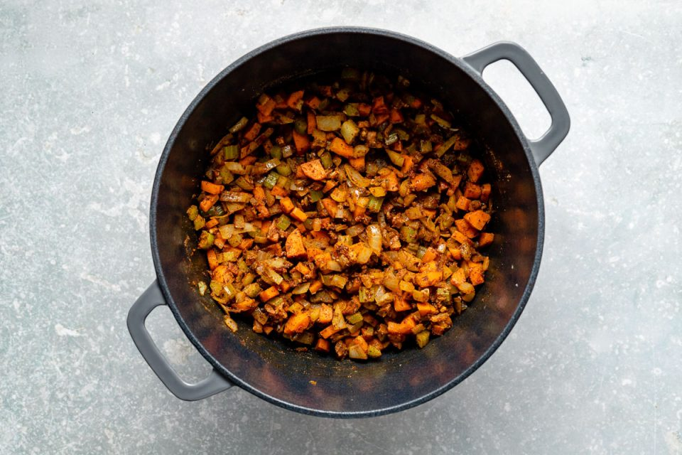 How to make lentil soup: Spices added to softened mirepoix shown in a large gray dutch oven atop a light blue surface.